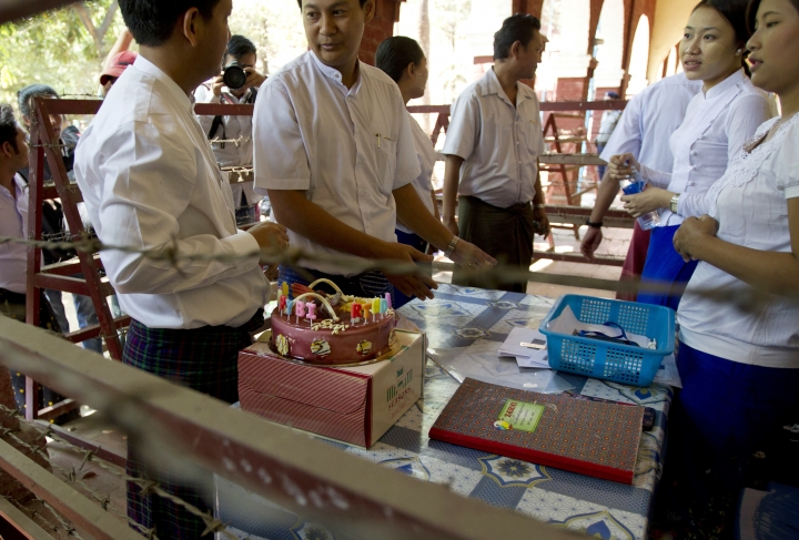 A local journalist, left, talks with the court officials as he try to send a birthday cake to Reuters journalist Wa Lone, unseen, at the trial Wednesday, April 11, 2018, Yangon, Myanmar. (AP Photo/Thein Zaw)