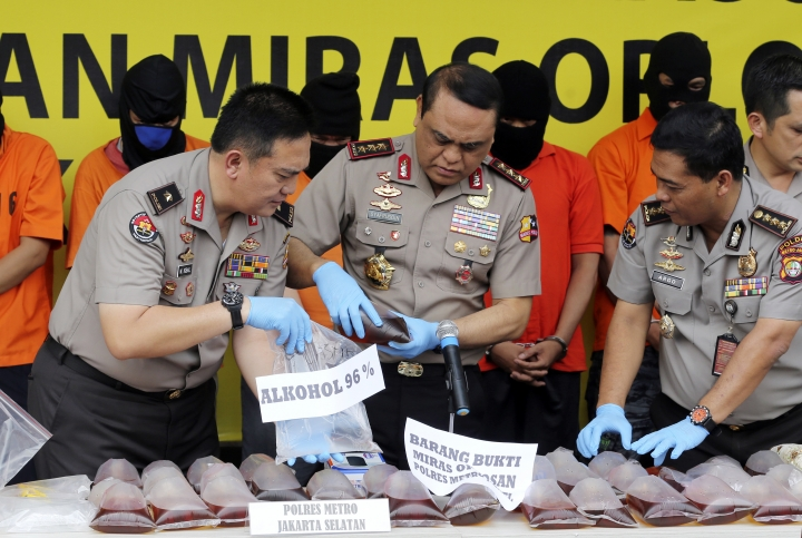 "Indonesian Deputy National Police Chief Muhammad Syafruddin, center, checks huge quantities of suspect confiscated alcohol during a press conference in Jakarta, Indonesia, Wednesday, April 11, 2018. Deaths from drinking toxic bootleg alcohol in Indonesia have exceeded 100 this month, police said Wednesday as they vowed a ""scorched earth"" crackdown on the makers and distributors of black-market liquor. (AP Photo/Tatan Syuflana)"
