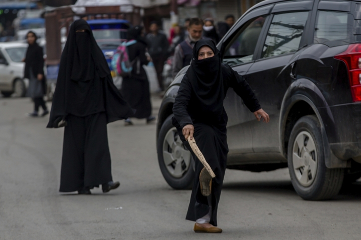 A burqa clad Kashmiri woman student, taunts an Indian police officer during a protest against the killing of civilians in Srinagar, Indian controlled Kashmir, Wednesday, April 11, 2018. Three men were killed in Kashmir when government forces fired on anti-India protesters who thronged a village following a gunbattle that killed three rebels and a soldier, officials said Wednesday. (AP Photo/Dar Yasin)
