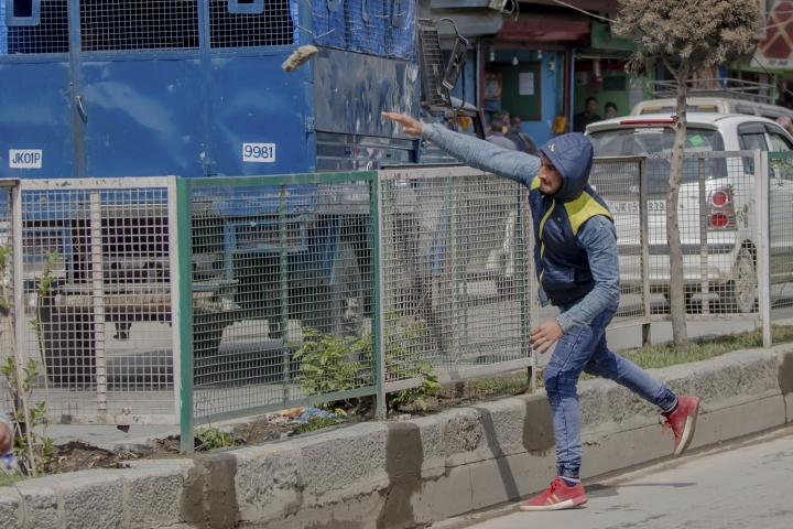 A Kashmiri protester throws stone at an Indian police vehicle during a protest against the killing of civilians in Srinagar, Indian controlled Kashmir, Wednesday, April 11, 2018. Three men were killed in Kashmir when government forces fired on anti-India protesters who thronged a village following a gunbattle that killed three rebels and a soldier, officials said Wednesday. (AP Photo/Dar Yasin)