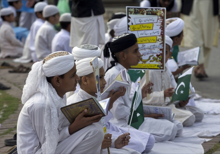 "Pakistani religious students affiliated with various Islamic seminaries read Quran and pray for the victims of a deadly April 2, 2018 airstrike by Afghan forces in the Afghan province of Kunduz, in Islamabad, Pakistan, Wednesday, April 11, 2018. An Afghan official said the airstrike was on a Taliban training camp in northern Afghanistan and killed at least 35 insurgents and wounded many more, while the Taliban said the airstrike hit a religious school during a graduation ceremony, killing dozens of civilians. Placard reads in part, ""These innocent children."" (AP Photo/B.K. Bangash)"