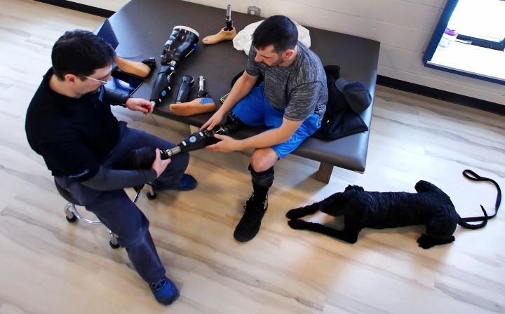 In this March 20, 2018 photo, prosthetist John Warren attaches a foot to Marc Fucarile's microprocessor controlled prosthetic knee during a visit to the Medical Center Orthotics and Prosthetics in the Allston neighborhood of Boston. In the five years since the Boston Marathon bombing, medical science has made promising advances in amputations and artificial limbs. (AP Photo/Charles Krupa)