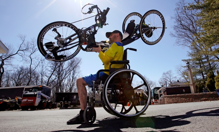 In this April 9, 2018 photo, Boston Marathon bombing survivor Marc Fucarile carries his racing handcycle to a road while preparing to train in Reading, Mass. for this year's Boston Marathon. (AP Photo/Charles Krupa)