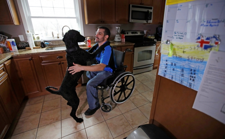 In this April 4, 2018, photo, Boston Marathon bombing survivor Marc Fucarile pats his dog Onyx at his home in Reading, Massachusetts. The 39-year-old from the Boston area lost his right leg in the blast, and his badly maimed left leg causes him unceasing pain. He fears another amputation might be his only option. (AP Photo/Charles Krupa)