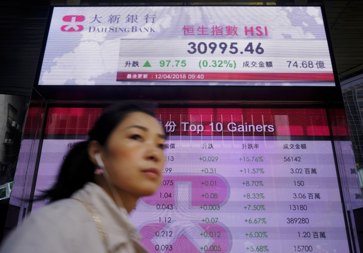 A woman walks past an electronic board showing Hong Kong share index outside a local bank in Hong Kong, Thursday, April 12, 2018. Asian shares were mixed Thursday as investors digested the latest Fed minutes while geopolitical concerns overshadowed sentiment after President Donald Trump struck a defiant tone on the Middle East conflict. (AP Photo/Vincent Yu)