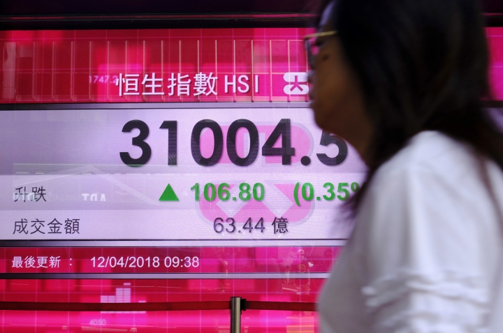 A woman walks past an electronic board showing Hong Kong share index outside a local bank in Hong Kong, Thursday, April 12, 2018. Asian shares were mixed Thursday as investors digested the latest Fed minutes while geopolitical concerns overshadowed sentiment after President Donald Trump struck a defiant tone on the Middle East conflict.(AP Photo/Vincent Yu)