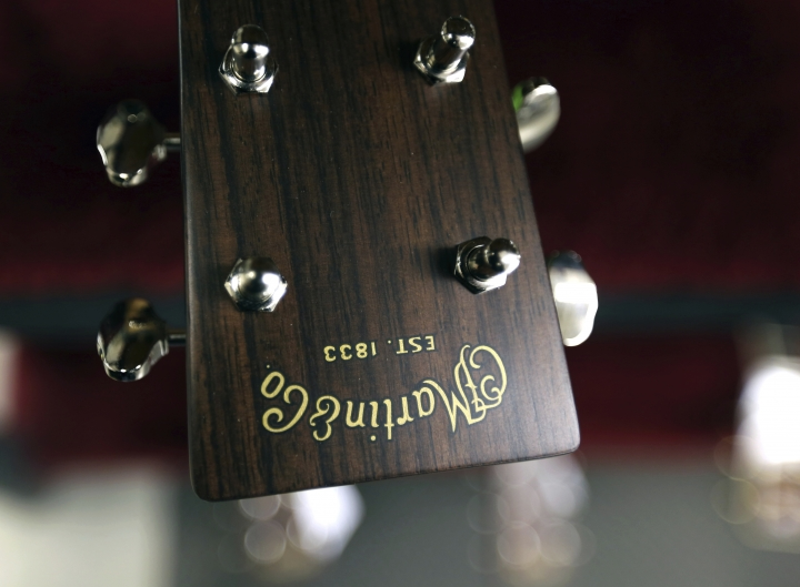 In this Friday, March 23, 2018 photo, a C. F. Martin and Co. logo adorns a rosewood headstock on a guitar on the factory floor at C. F. Martin and Co., in Nazareth, Pa. Fearful that parts of Africa and Asia were losing their rosewood forests to illegal loggers, governments in 2016 banded together to slap international trade regulations on hundreds of species of the trees. (AP Photo/Jacqueline Larma)