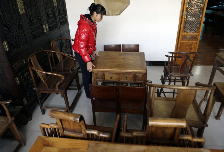 FILE - In this Oct. 23, 2012, file photo, a salesperson adjusts a table made from Hainan rosewood at a furniture shop in Beijing. To help stem the loss of rosewood forests in Africa and Asia, governments adopted rules to stem the flow of smuggled rosewood to China's luxury furniture manufacturers. But the restrictions have also hurt companies that use relatively tiny amounts of the wood in guitars, clarinets and oboes. (AP Photo/Ng Han Guan, File)