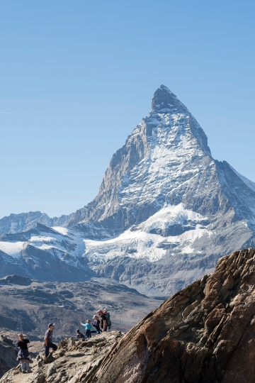 In this Oct. 16, 2017 file photo people stand in front of the Matterhorn near in Zermatt, Switzerland. Authorities in Switzerland and Italy were searching Wednesday April 11, 2018 for a German billionaire who has been missing in the Alps since the weekend, when he failed to return from a ski excursion on the Matterhorn. Karl-Erivan Haub, heir to the Tengelmann retail empire, was training for a ski race when he disappeared on Switzerland's famous peak, located on the border with Italy. (Cyril Zingaro/Keystone via AP,file)