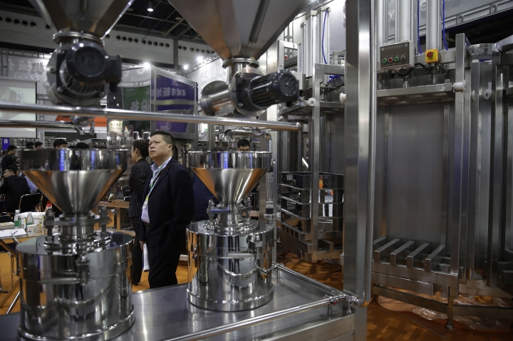 Visitors look at a Chinese company displaying industrial machinery used for processing soybean at the International soybean exhibition in Shanghai, Thursday, April 12, 2018. China's government has denied President Xi Jinping's promises this week to cut import tariffs on cars and open China's markets wider were intended as an overture to settle a tariff dispute with Washington. A commerce ministry spokesman said negotiations were impossible under 'unilateral coercion' by President Donald Trump's government. (AP Photo/Andy Wong)