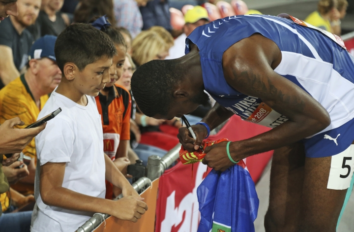 Kyron Mcmaster of the British Virgin Islands signs on a pair of his shoes for a young fan after winning the gold medal in the men's 400m hurdles final at Carrara Stadium during the Commonwealth Games on the Gold Coast, Australia, Thursday, April 12, 2018. (AP Photo/Dita Alangkara)