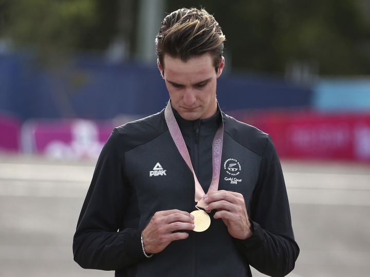 New Zealand's Samuel Gaze looks down at his medal after winning gold in the men's cross-country race at the Nerrang mountain bike trails during the 2018 Commonwealth Games on the Gold Coast, Australia, Thursday, April 12, 2018. (AP Photo/Rick Rycroft)