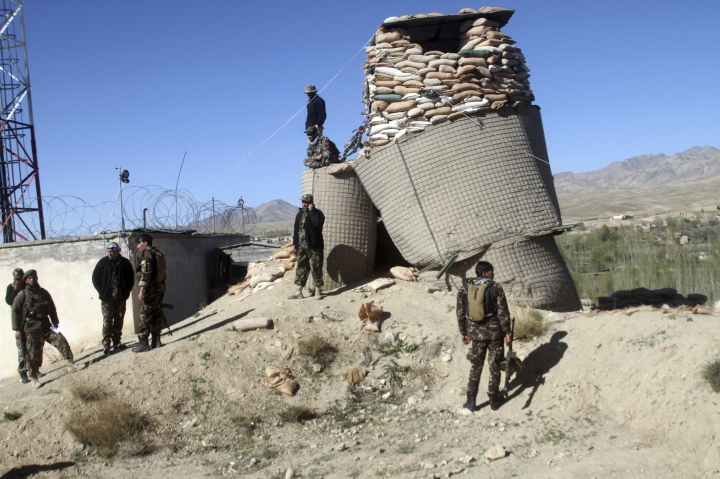 Afghan security personnel stand guard near to Khuja Omari district compound after a deadly Taliban attack in Ghazni, Afghanistan, Thursday, April 12, 2018. The Taliban claimed responsibility for a blistering attack early Thursday morning on a government compound in Afghanistan's central province of Ghazni that killed at least 15 members of the security forces. (AP Photos/Rahmatullah Nikzad)