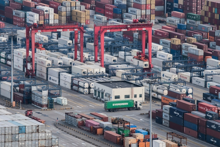 In this March 29, 2018 photo, a cargo truck drives amid stacked shipping containers at the Yangshan port in Shanghai. China's global trade balance swung to a rare deficit in March as exports shrank but its surplus with the United States, the center of a worsening dispute with Washington, stood at $15.4 billion.(AP Photo/File)