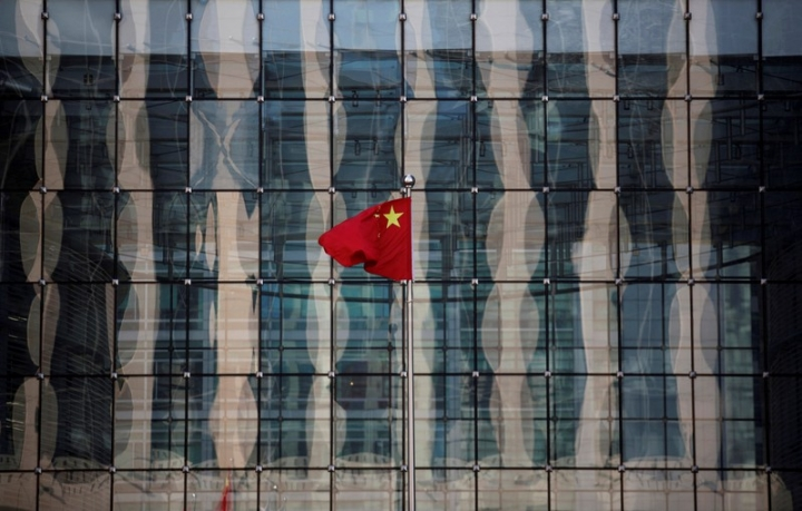 FILE PHOTO: A Chinese national flag flutters at the headquarters of a commercial bank on a financial street in central Beijing, China November 24, 2014.    REUTERS/Kim Kyung-Hoon/File Photo