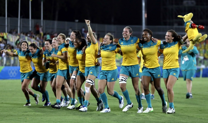 FILE - In this Aug. 8, 2016 file photo, Australian players celebrate after winning the women's rugby sevens gold medal match against New Zealand at the Summer Olympics in Rio de Janeiro, Brazil. Australia coach Tim Walsh has gone to extreme lengths to prepare his squad for the inaugural games medal of women's rugby, including hosing down footballs. (AP Photo/Themba Hadebe,File)
