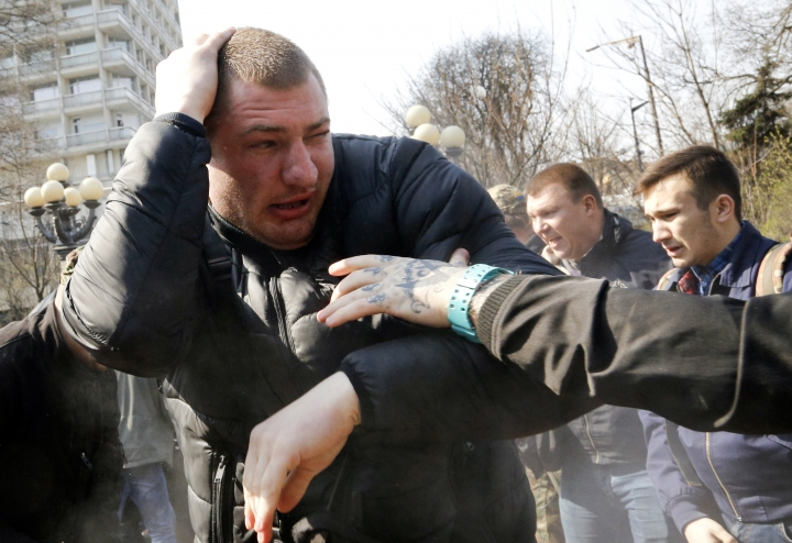 An ultra-right activists fights with pro-Russian supporters at the Soviet-era monument to General NIkolai Vatutin in Kiev, Ukraine, Friday, April 13, 2018. Activists of the Right Sector group on Friday splashed red paint on the Soviet-era monument to Nikolai Vatutin, a Red Army general who died in fighting during WW II. They also engaged in scuffles with supporters of an opposition party who attempted to put flowers to the monument in the Ukrainian capital, Kiev. (AP Photo/Efrem Lukatsky)