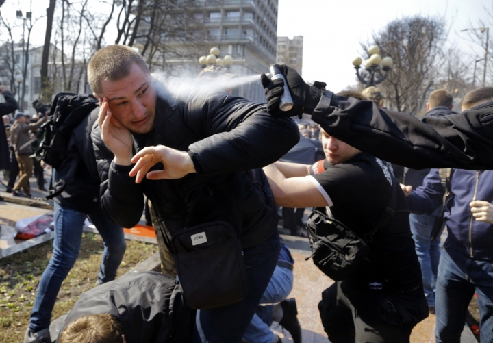An ultra-right activist is sprayed with tear gas during clashes with pro-Russian supporters, at the Soviet-era monument to General NIkolai Vatutin in Kiev, Ukraine, Friday, April 13, 2018. Activists of the Right Sector group on Friday splashed red paint on the Soviet-era monument to Nikolai Vatutin, a Red Army general who died in fighting during WW II. They also engaged in scuffles with supporters of an opposition party who attempted to put flowers to the monument in the Ukrainian capital, Kiev. (AP Photo/Efrem Lukatsky)