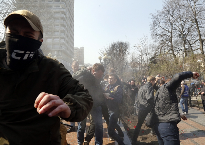 Ultra-right activists fight with pro-Russian supporters, at the Soviet-era monument to General NIkolai Vatutin in Kiev, Ukraine, Friday, April 13, 2018. Activists of the Right Sector group on Friday splashed red paint on the Soviet-era monument to Nikolai Vatutin, a Red Army general who died in fighting during WW II. They also engaged in scuffles with supporters of an opposition party who attempted to put flowers to the monument in the Ukrainian capital, Kiev. (AP Photo/Efrem Lukatsky)