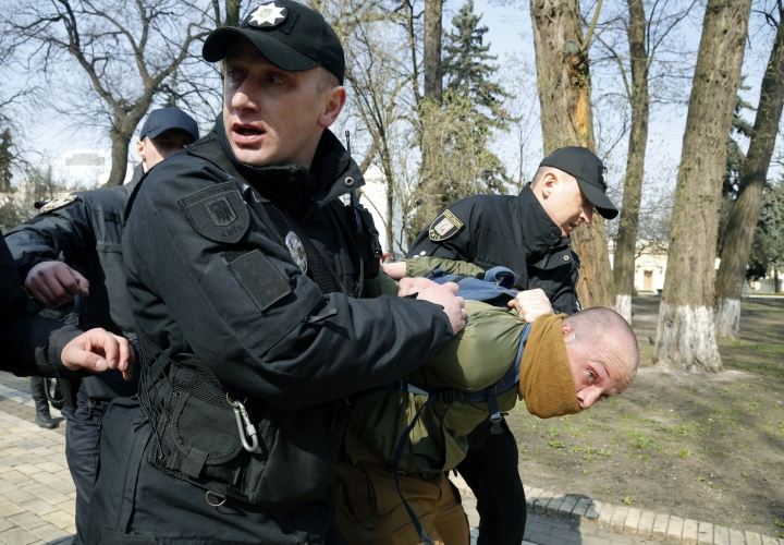 Policemen detain an ultra-right activist after clashes with pro-Russian supporters at the Soviet-era monument to General NIkolai Vatutin in Kiev, Ukraine, Friday, April 13, 2018. Activists of the Right Sector group on Friday splashed red paint on the Soviet-era monument to Nikolai Vatutin, a Red Army general who died in fighting during WW II. They also engaged in scuffles with supporters of an opposition party who attempted to put flowers to the monument in the Ukrainian capital, Kiev. (AP Photo/Efrem Lukatsky)