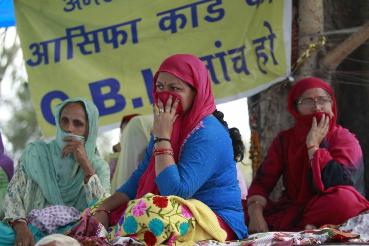 Village women sit on a hunger strike demanding that the investigation into the rape and murder of 8-year-old girl Asifa be handed over to the Central Bureau of Investigation (CBI), claiming that the six Hindu men accused in the attack had been framed and that the police investigation was flawed, in Kathua, India, Friday, April 13, 2018. Thousands of members of a radical Hindu group have marched to demand the release of the six men accused of repeatedly raping the Muslim girl inside a Hindu temple. On Monday, Hindu lawyers in Kathua tried to block police from filing their investigation report at the local court. (AP Photo/Channi Anand)