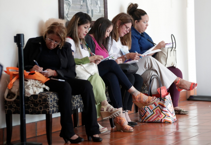 FILE- In this Tuesday, Jan. 30, 2018, file photo, women fill out job applications at a JobNewsUSA job fair in Miami Lakes, Fla. On Friday, April 13, 2018, the Labor Department reports on job openings and labor turnover for February. (AP Photo/Lynne Sladky, File)
