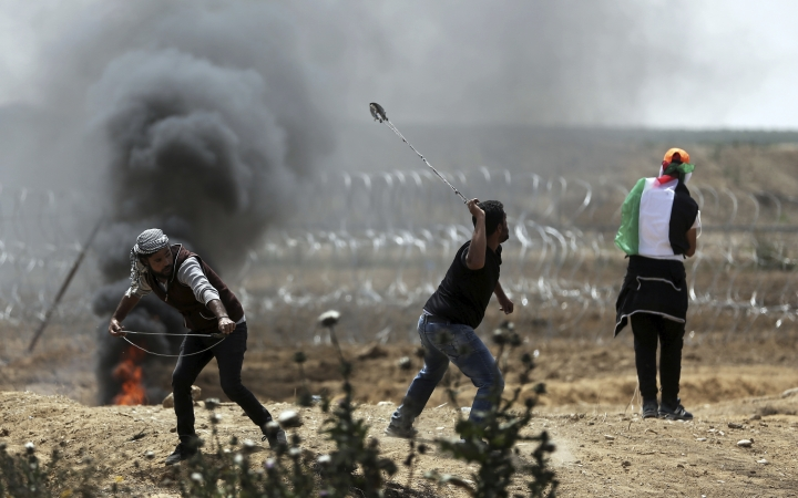 Palestinian protesters hurl stones at Israeli troops during a protest at the Gaza Strip's border with Israel, Friday, April 13, 2018. (AP Photo/ Khalil Hamra)