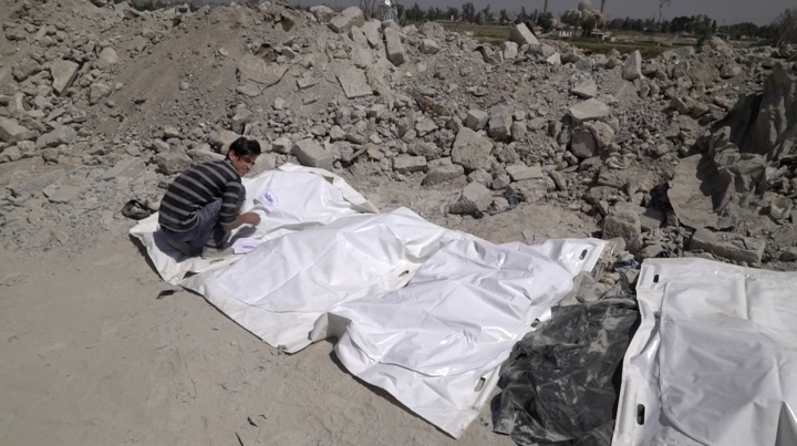 In this image made from video taken on Monday, April 9, 2018, a volunteer covers bodies recovered in Mosul's Old City. A city official says more than 1,000 bodies, most of them believed to be Islamic State group fighters killed in the militants' last stand in Mosul, have been buried in a mass grave outside the city. (AP Photo/Balint Szlanko)