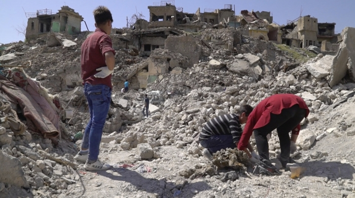 In this image made from video taken on Monday, April 9, 2018, volunteers recover human remains in Mosul's Old City. A city official says more than 1,000 bodies, most of them believed to be Islamic State group fighters killed in the militants' last stand in Mosul, have been buried in a mass grave outside the city.(AP Photo/Balint Szlanko)