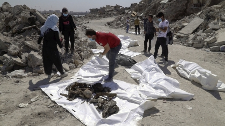 In this image made from video taken on Monday, April 9, 2018, volunteers place human remains into body bags in Mosul's Old City. A city official says more than 1,000 bodies, most of them believed to be Islamic State group fighters killed in the militants' last stand in Mosul, have been buried in a mass grave outside the city. (AP Photo/Balint Szlanko)