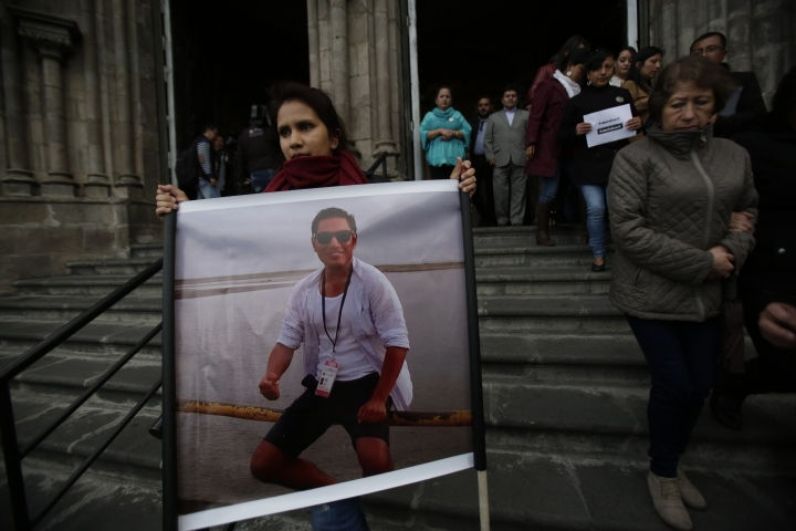 A relative of journalist Javier Ortega, member of a team of El Comercio employees who were kidnapped on the Ecuador-Colombia border 11 days ago, holds his picture after a Mass in honor of the group in Quito, Ecuador, Thursday, April 5, 2018. (AP Photo/Dolores Ochoa)