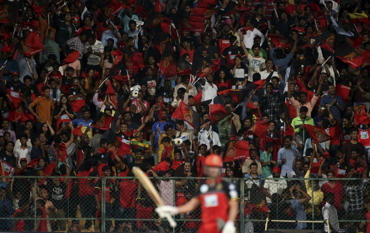 Supporters of Royal Challengers Bangalore cheer to applaud batsman AB de Villiers, foreground, after he scored fifty runs during the VIVO IPL Twenty20 cricket match against Kings XI Punjab in Bangalore, India, Friday, April 13, 2018. (AP Photo/Aijaz Rahi)