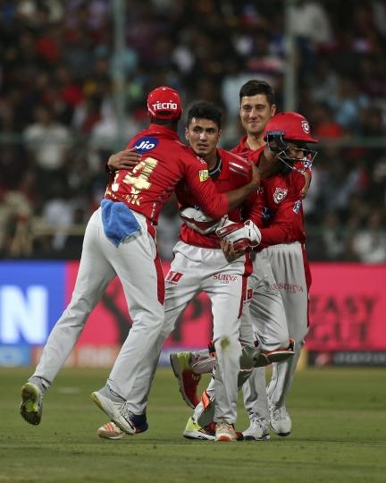 Kings XI Punjab bowler Mujeeb ur Rahman, second left, celebrates with teammates the dismissal of Royal Challengers Bangalore captain Virat Kohli during their VIVO IPL Twenty20 cricket match in Bangalore, India, Friday, April 13, 2018. (AP Photo/Aijaz Rahi)