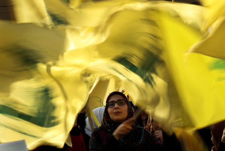 "A Hezbollah supporter waves her group flags during an election campaign speech by Hezbollah leader Sayyed Hassan Nasrallah, in a southern suburb of Beirut, Lebanon, Friday, April 13, 2018. Nasrallah says Monday's attack on the T4 air base ushers in a new phase that puts Israel in a state of ""direct confrontation"" with the Islamic Republic of Iran. (AP Photo/Hussein Malla)"