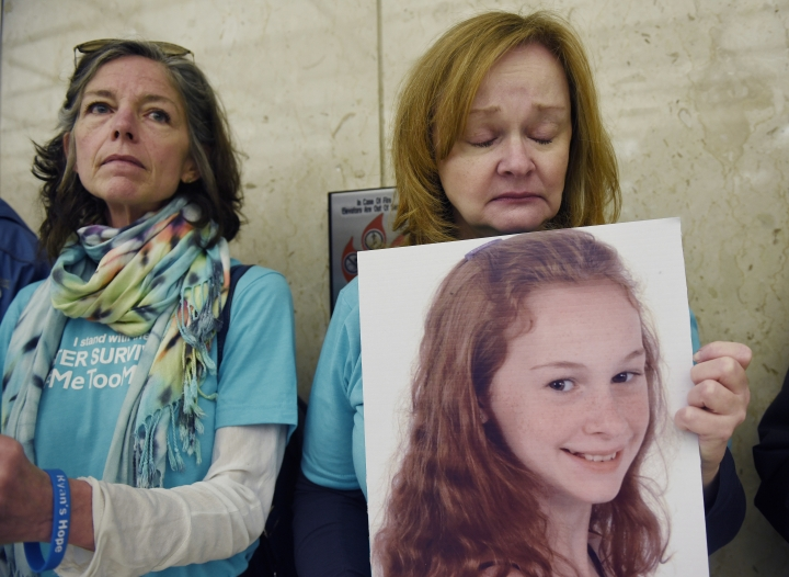 Valerie von Frank, right, of Okemos, Mich., holds a portrait of her daughter Grace French, a sexual abuse survivor, while waiting at the elevator to greet arriving trustees for a Michigan State University board meeting, Friday, April 13, 2018, Lansing, Mich. Interim Michigan State University President John Engler said Friday that he regrets the school's response to a woman filing a federal rape lawsuit against the university. (Clarence Tabb Jr./Detroit News via AP)
