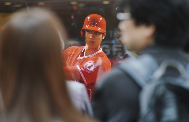 In this April 4, 2018 photo, pedestrians in Tokyo watch a TV showing the live broadcasting of Los Angeles Angels' Shohei Ohtani, of Japan, gets ready to bat during a baseball game against the Cleveland Indians. Shohei Ohtani's games are shown live in the morning by national broadcaster NHK. In the afternoon, talk shows dissect his every move while evening sports programs feature highlights of his latest accomplishments. (AP Photo/Eugene Hoshiko)