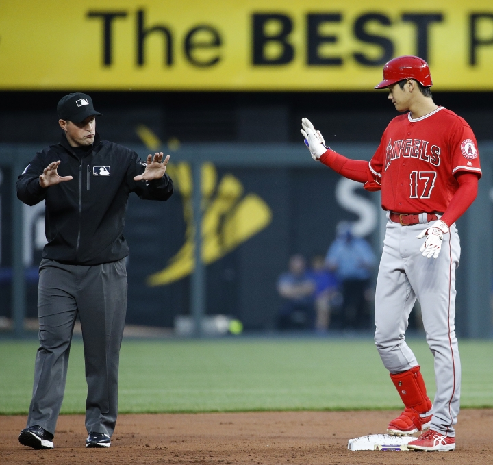Los Angeles Angels' Shohei Ohtani, right, talks to second base umpire Quinn Wolcott after hitting a double during the second inning of a baseball game against the Kansas City Royals, Friday, April 13, 2018, in Kansas City, Mo. (AP Photo/Charlie Riedel)