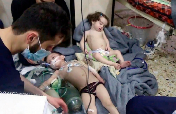 FILE - This Sunday, April 8, 2018 file image made from video released by the Syrian Civil Defense White Helmets, shows medical workers treating toddlers following an alleged poison gas attack in the opposition-held town of Douma, near Damascus, Syria. With the Middle East on edge and many fearing inadvertent triggering of regional war, it is easy to forget that two weeks ago Trump shocked advisers in declaring an intention to withdraw troops from Syria. Now, apparently angered by a suspected chemical attack, Trump is threatening imminent military strikes against the Syrian government forces he blames and rattling a saber at Syria's patron Russia. (Syrian Civil Defense White Helmets via AP, File)