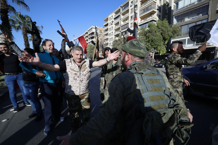 Syrian soldier wave weapons and dance as they chant slogans against U.S. President Trump during demonstrations following a wave of U.S., British and French military strikes to punish President Bashar Assad for suspected chemical attack against civilians, in Damascus, Syria, Saturday, April 14, 2018. Hundreds of Syrians are demonstrating in a landmark square in the Syrian capital, waving victory signs and honking their car horns in a show of defiance. (AP Photo/Hassan Ammar)