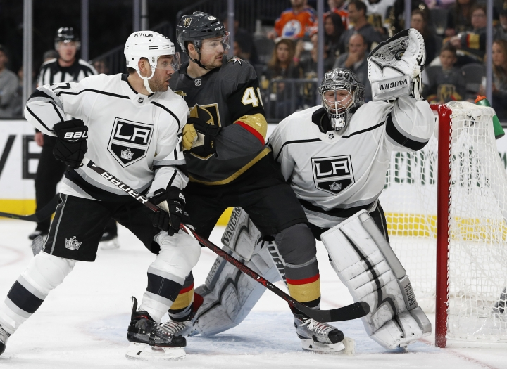 Los Angeles Kings goaltender Jonathan Quick makes a save beside Vegas Golden Knights center Ryan Carpenter, center, and Los Angeles Kings defenseman Alec Martinez, left, during the first overtime of Game 2 of an NHL hockey first-round playoff series, Friday, April 13, 2018, in Las Vegas. (AP Photo/John Locher)