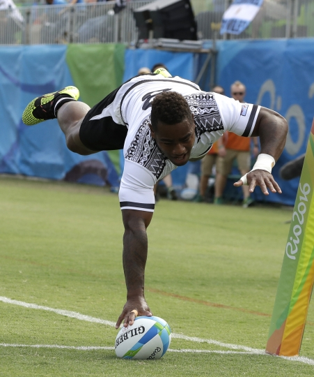 FILE - In this Aug. 11, 2016 file photo, Fiji's Josua Tuisova, scores a try during the semifinal men's rugby sevens match against Japan at the Summer Olympics in Rio de Janeiro, Brazil.The Fijian netball team went missing on the Gold Coast Saturday, April 14, 2018 and failed to turn up to watch the semifinals of their Commonwealth Games sport. They were found further south at the rugby sevens where the Olympic champion Fijian men began their campaign with a 63-5 win over Sri Lanka. (AP Photo/Themba Hadebe,File)