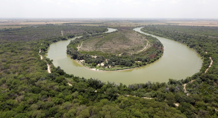 FILE - In this July 24, 2014, file photo, a bend in the Rio Grand is viewed from a Texas Department of Public Safety helicopter on patrol over in Mission, Texas. As hundreds of National Guard troops deploy to the U.S-Mexico border, residents of Texas' southernmost border region are fearful of the impact President Donald Trump's border wall will have. The troops patrolling the Rio Grande will eventually withdraw, but a wall could change the river forever. (AP Photo/Eric Gay, Pool, File)