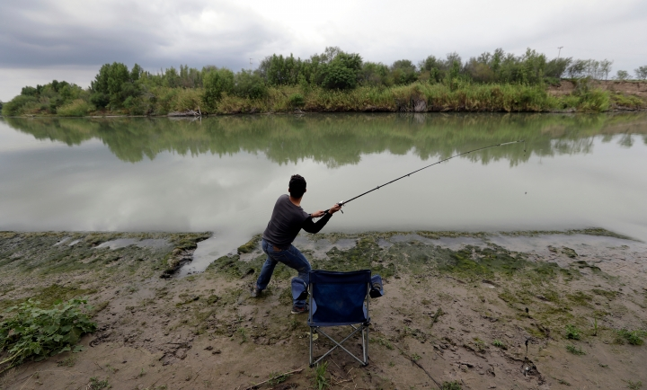 FILE - In this Nov. 12, 2016, file photo, Isac Ramos fishes at a ranch on the banks of the Rio Grande in Los Ebanos, Texas. As hundreds of National Guard troops deploy to the U.S-Mexico border, residents of Texas' southernmost border region are fearful of the impact President Donald Trump's border wall will have. The troops patrolling the Rio Grande will eventually withdraw, but a wall could change the river forever. (AP Photo/Eric Gay, File)