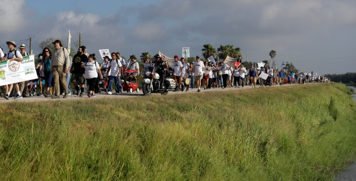 FILE - In this Aug. 12, 2017, file photo, hundreds of people march along a levee in South Texas toward the Rio Grande to oppose the wall the U.S. government wants to build on the river separating Texas and Mexico, in Mission, Texas. As hundreds of National Guard troops deploy to the U.S-Mexico border, residents of Texas' southernmost border region are fearful of the impact President Donald Trump's border wall will have. The troops patrolling the Rio Grande will eventually withdraw, but a wall could change the river forever. (AP Photo/Eric Gay, File)
