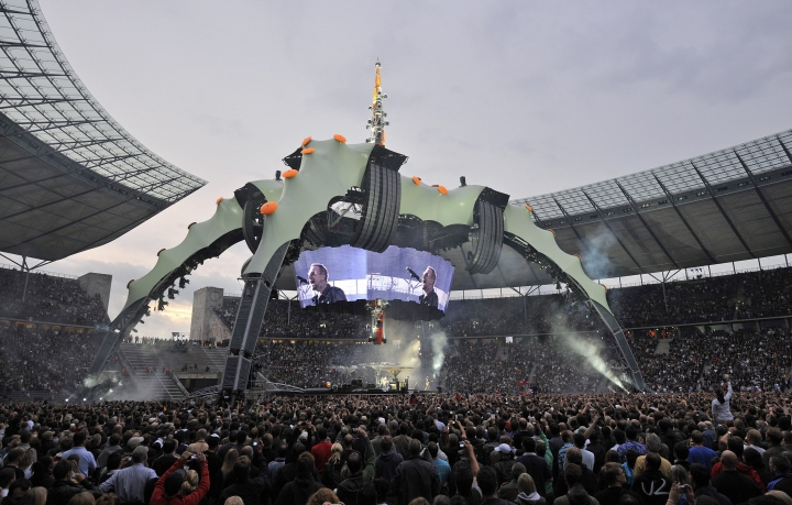 FILE- In this July 18, 2009 file photo, U2 with singer Bono, seen on the TV screen, perform during their 360 degree Tour at the Olympic Stadium in Berlin, Germany. The former stage centerpiece of rock band U2's international tour, a 165-foot tall spider-like structure, has found a new home as the backdrop for an aquarium expansion in suburban Salt Lake City. (AP Photo/Gero Breloer, File)