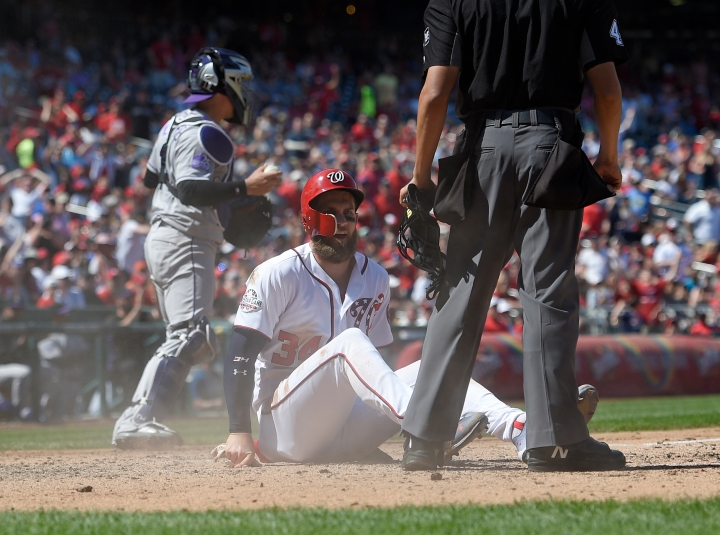 Washington Nationals' Bryce Harper (34) sits on the dirt after he slid home during the sixth inning of a baseball game against the Colorado Rockies Saturday, April 14, 2018, in Washington. Colorado Rockies catcher Tony Wolters, is seen at back. Harper was originally called out at the plate but was safe when the call was overturned by replay. The Nationals won 6-2. (AP Photo/Nick Wass)