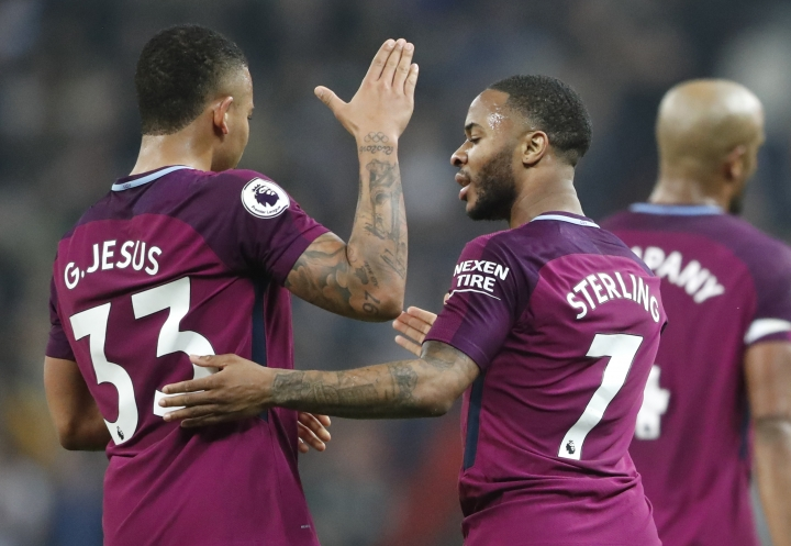 Manchester City's Gabriel Jesus, left, celebrates with Raheem Sterling after scoring his sides third goal during the English Premier League soccer match between Tottenham Hotspur and Manchester City at Wembley stadium in London, England, Saturday, April 14, 2018. (AP Photo/Frank Augstein)