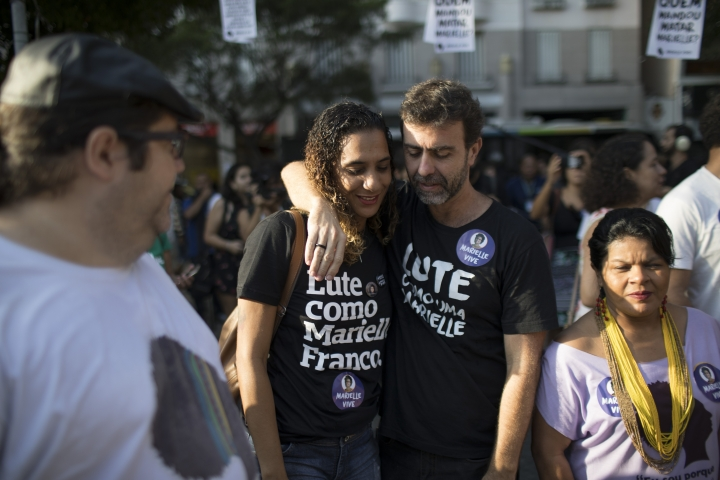 Rio state Congressman Marcelo Freixo embraces Anielle Franco, left, sister of councilwoman Marielle Franco during a memorial for Marielle Franco and her driver Anderson Pedro Gomes, who both were killed a month ago in Rio de Janeiro, Brazil, Saturday, April 14, 2018. Franoco's death has touched a nerve with many in a nation where more than 50 percent identify as black or mixed race, but where most politicians are white men. (AP Photo/Leo Correa)