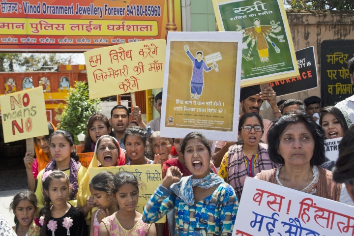 "Indian women shout slogans during a protest gathering organised by a non governmental organization to condemn violence against women in Dharmsala, India, Sunday, April 15, 2018. Violent crimes against women have been on the rise in India despite tough laws enacted in 2013. Placard in Hindi reads, ''We will protest- We will demand accountability"", center top and "" Enough, we will now not tolerate violent men"", bottom, right. (AP Photo/Ashwini Bhatia)"