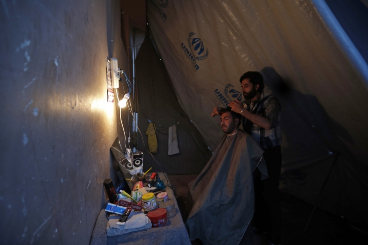 In this Friday, April 13, 2018 photo, a man who was displaced with his family from eastern Ghouta receives a haircut at a roadside makeshift barbershop at a displaced shelter, in the village of Horjelli in the Damascus countryside, Syria. Thousands of Syrians displaced by the battle for the once-lush suburbs of Damascus now find themselves in a crowded settlement, where for the first time in recent memory they have enough to eat. The community is home to some 18,000 people displaced by the offensive that drove rebels out of eastern Ghouta. On Saturday, the Syrian government announced the capture of Douma, the last rebel stronghold in eastern Ghouta and the site of an alleged chemical attack that prompted a Western missile strike. (AP Photo/Hassan Ammar)